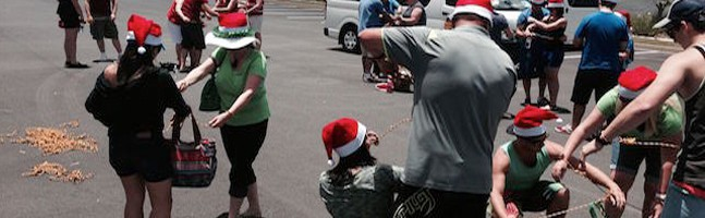 people completing tasks with santa hats on in the amazing race challenge for their christmas party