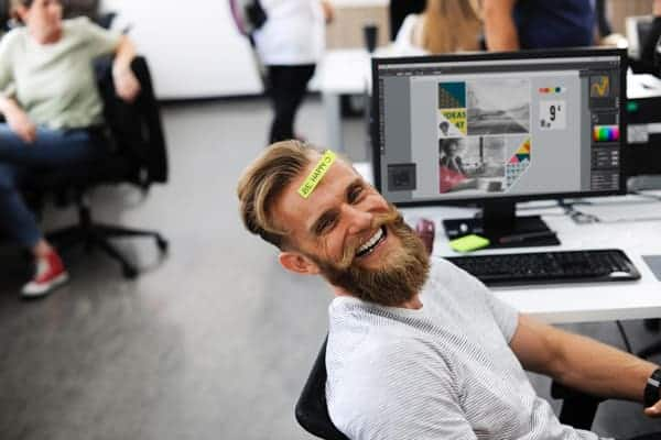 man smiling in an office that has good workplace culture